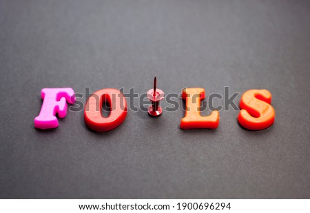 The word fools from color letters with a pushpin on a black background. April Fools' Day, April 1, not trusting anyone, jokes.