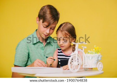 Children paint a picture while sitting at a table on a yellow background. Brother teaches little sister to draw with crayons. Studio photo