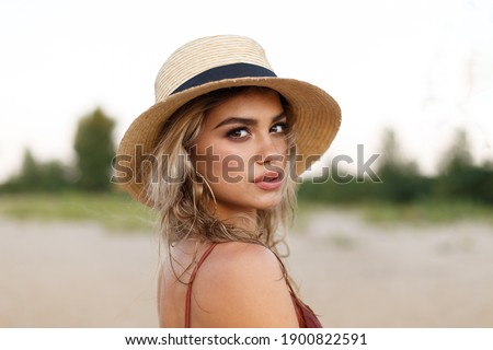 Young beautiful girl in a straw hat on vacation. Close-up portrait of a girl with a beautiful face.