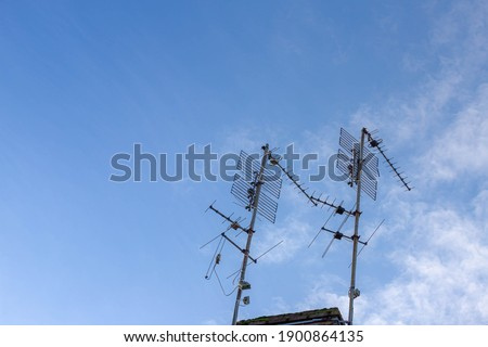 Old analog TV antenna mast pole on the rooftop of the house under blue sky and white clouds, Radio engineering used with a transmitter or receiver signal. Royalty-Free Stock Photo #1900864135