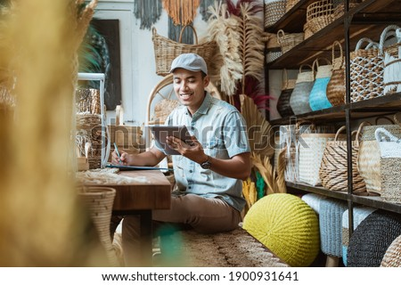 The shop owner notes with a pen while using a digital tablet while sitting in a craft store Royalty-Free Stock Photo #1900931641