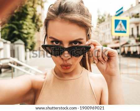 Beautiful smiling model in summer casual clothes.Sexy carefree female posing in the street in sunglasses.Taking selfie self portrait photos on smartphone. Making duck face