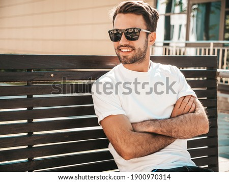 Portrait of handsome smiling stylish hipster lambersexual model.Man dressed in white T-shirt. Fashion male sitting at the bench in the street background in sunglasses. Crossed arms Royalty-Free Stock Photo #1900970314