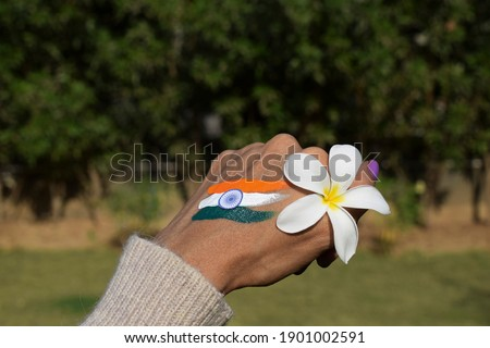 Female with Indian flag tri color tattoo on back of hand on occasion of Indian republic day holding white flower that symbolize peace. Celebrating India republic day at home