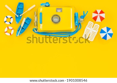 Miniatures of beach equipment and a stylish camera for underwater photos, umbrellas, boats, sun loungers. blank yellow background with space for text, concept, Sunny beach vacation. Royalty-Free Stock Photo #1901008546