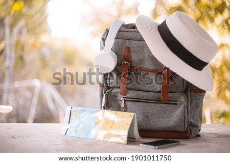 Bag, hat, map and headphones on Vacation day. Royalty-Free Stock Photo #1901011750