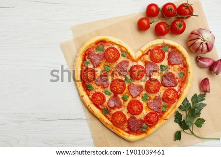 Heart shaped Italian pizza with salami,cherry tomatoes,garlics,parsley,pizza sauce,mozzella and olive oil on parchment paper with white wood table background.Love concept for Valentine's day