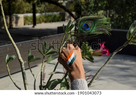 Person celebrating Indian republic day by painting Indian flag tri colored tattoo in hand and holding white flowers to depict unity, freedom and peace.