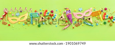 Purim celebration concept (jewish carnival holiday) over wooden green background. Top view, flat lay