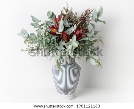 Beautiful flower arrangement of mostly Australian native flowers, including, Silvan Reds, Wattle foliage and Eucalyptus leaves, in a white and blue strip vase, with a white background. Royalty-Free Stock Photo #1901121160