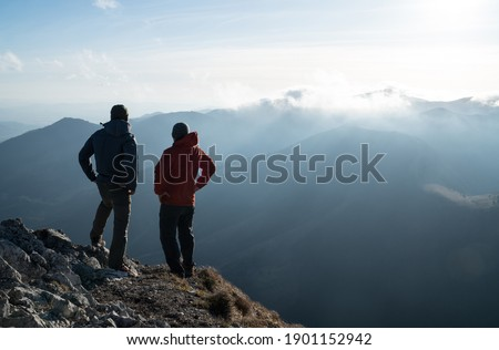Two men standing standing with trekking poles on cliff edge and looking at sunset rays over the clouds. Successful summit concept image. Royalty-Free Stock Photo #1901152942