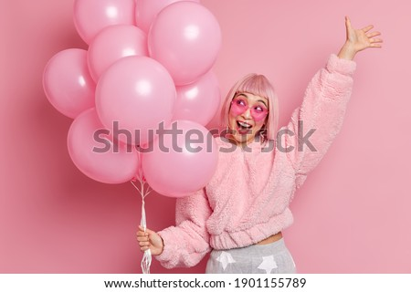 Overjoyed pretty Asian girl with pink hair dressed in fashionable coat raises hand has fun on party celebrates anniversary holds inflated balloons isolated over pink background. Partying concept