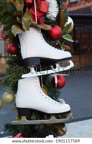 White skates for figure skating hang against a background of fir branches and toys. Christmas balls decorate the background of the white skates.
