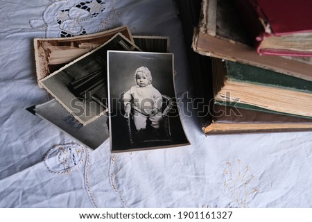 old photo albums lie on a white mint tablecloth, vintage photographs of 1960, concept of family tree, genealogy, childhood memories, connection with ancestors Royalty-Free Stock Photo #1901161327