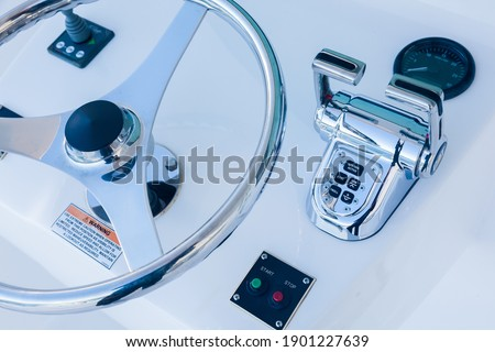 Motor yacht control panel. Steering wheel, gear levers, control button tachometer. Luxury yacht navigation bar. Royalty-Free Stock Photo #1901227639