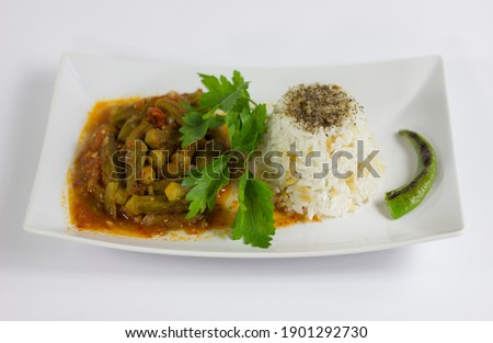 Okra with rice pilaf and parsley in a white plate