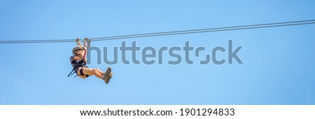 Teenager having fun on a zipline on panoramic blue sky background with copy space. Royalty-Free Stock Photo #1901294833