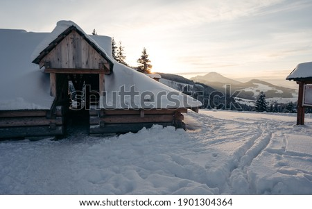 Snow covered wooden cabin facing the snowy peaks of mountains in the cold winter. Winter mountain landscape with wooden house on sunny clear day.
