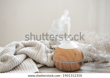 Aroma composition with a modern aroma oil diffuser on a wooden surface with a knitted element and a sprig of dried flowers. Royalty-Free Stock Photo #1901312350