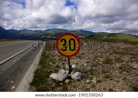 30 kilometers per hour speed limitation sign at the entry of the Ranca mountain resort on Transalpina alpine road in Gorj country, Romania. Speed management used across residential areas.