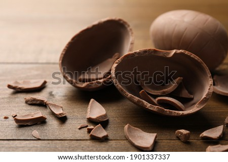 Broken and whole chocolate egg on wooden table, closeup Royalty-Free Stock Photo #1901337337