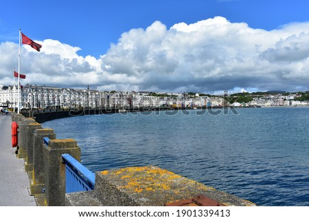 A view of the capital of Isle of Man, Douglas. Manx flags are flying and we can see a row of identical white buildings in line. There is a fairground along the promenade. Royalty-Free Stock Photo #1901339413