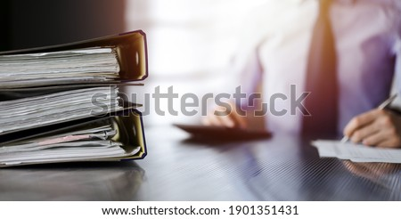 Binders with papers are waiting to be processed by unknown man accountant in blue shirt staying at home during covid pandemic Royalty-Free Stock Photo #1901351431
