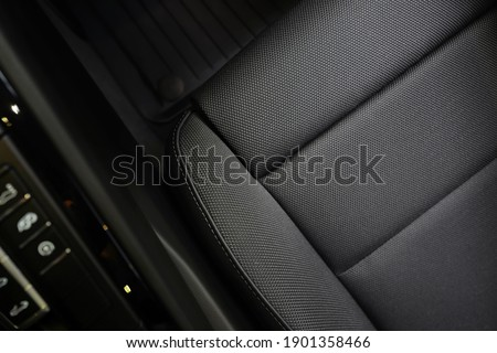 High angle view of luxury sport car front passenger seat and detail high end fabric and stitch texture along with blurred gear shift control buttons. Design element and car interior background. Royalty-Free Stock Photo #1901358466