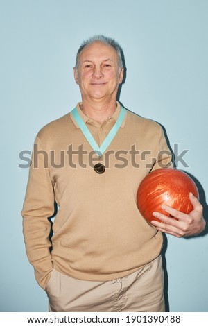 Vertical waist up portrait of smiling senior man holding bowling ball while standing against blue background, shot with flash