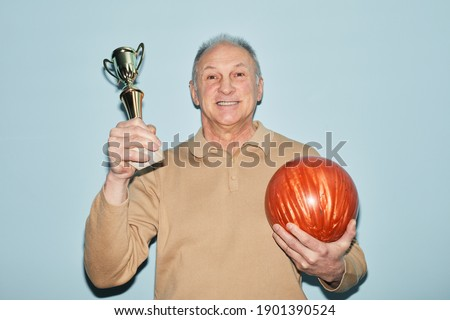 Waist up portrait of smiling senior man holding trophy and bowling ball while standing against blue background, shot with flash, copy space