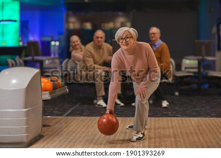Full length portrait of joyful senior woman playing bowling with group of friends in background, copy space