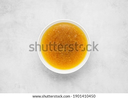 Bone bouillon in white bowl, beef broth on gray concrete background, top view, flat lay, minimalism Royalty-Free Stock Photo #1901410450