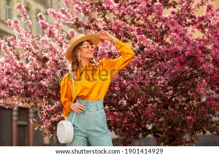Happy smiling woman wearing trendy straw hat, yellow satin blouse, blue trousers, cat eye sunglasses, with wicker bag, posing in street near pink spring blossom trees. Copy, empty space for text  Royalty-Free Stock Photo #1901414929