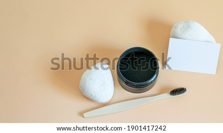 Branding mockup template with activated organic charcoal powder, natural stones and business card for displaying your logo. Teeth whitening, health care concepts.