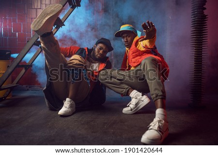 Serious rappers with gold jewelry poses in studio Royalty-Free Stock Photo #1901420644