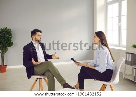 Young man sitting on chair in television studio and giving interview to journalist. Happy smiling TV host with microphone talking to famous person and asking questions about his opinion and experience