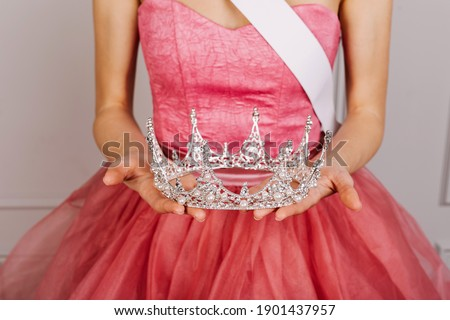 Closeup of a woman in tulle dress, holding a diamond crown. Beauty contest winner. Royalty-Free Stock Photo #1901437957