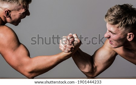 Arm wrestling. Two men arm wrestling. Rivalry, closeup of male arm wrestling. Two hands. Men measuring forces, arms. Hand wrestling, compete. Hands or arms of man.