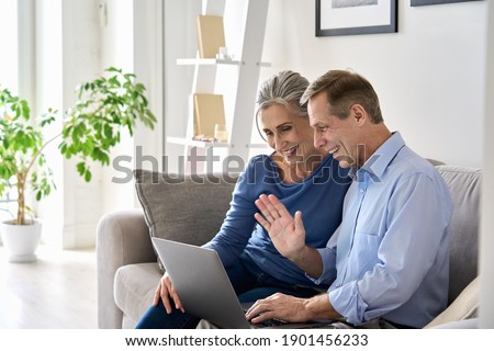 Happy old senior grandparents couple waving hand making online video call enjoying family virtual meeting digital webcam videocall chat talking, looking at laptop computer sitting on couch at home. Royalty-Free Stock Photo #1901456233