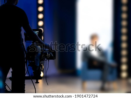 Cameraman filming in tv talk show studio. The host or presenter sitting on a chair camera pointed at him. Television news live broadcast production set