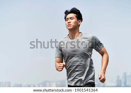 young asian man male runner jogger running jogging outdoors Royalty-Free Stock Photo #1901541364