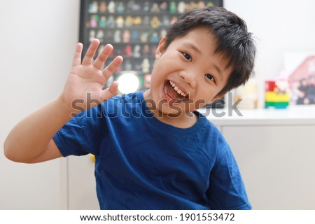 Front view of a little Asian boy waving hand and talking to the camera video calling video conference with his friend and family during the pandemic lockdown. Royalty-Free Stock Photo #1901553472
