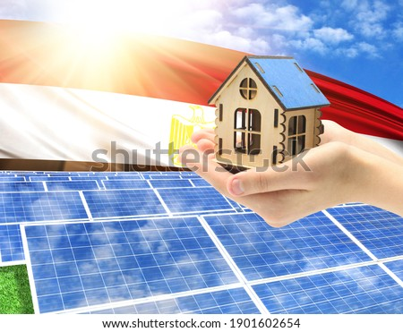 The photo with solar panels and a woman's palm holding a toy house shows the flag of Egypt in the sun.