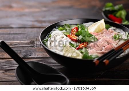 Vietnamese soup Pho Bo with beef and noodles on a wooden background, selective focus Royalty-Free Stock Photo #1901634559