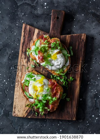 Sandwiches with smoked salmon, green salad and boiled egg on the dark background. Delicious breakfast, snack                 Royalty-Free Stock Photo #1901638870