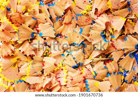 Sawdust from sharpening pencils fill the entire frame - Background image for text inscription - Shavings of colored pencils close-up - Concept of creativity and creation of art objects