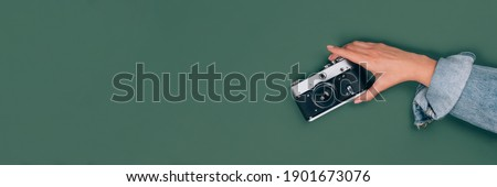 Banner with female hand holding old vintage photo camera on green background with copy space for text. Trendy vintage photography, Online photography school concept, selective focus