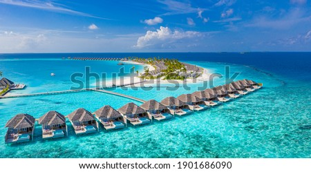 Maldives paradise scenery. Tropical aerial landscape, seascape with long jetty, water villas with amazing sea and lagoon beach, tropical nature. Exotic tourism destination banner, summer vacation Royalty-Free Stock Photo #1901686090