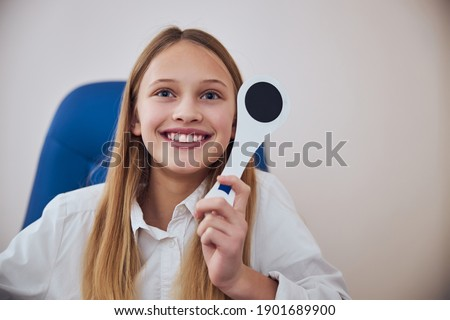 Close up portrait of good looking young blonde female child spending time in medicine center while checking eyesight in optometrist cabinet Royalty-Free Stock Photo #1901689900