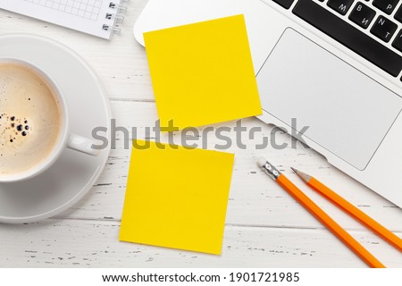 Office desk with yellow stickers, coffee and laptop. Remote office and work from home concept. Top view flat lay with copy space Royalty-Free Stock Photo #1901721985